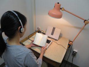 録音の様子。防音の部屋にスタンドライト、書見台、録音機器が用意され、静かな環境で録音図書を作成します。